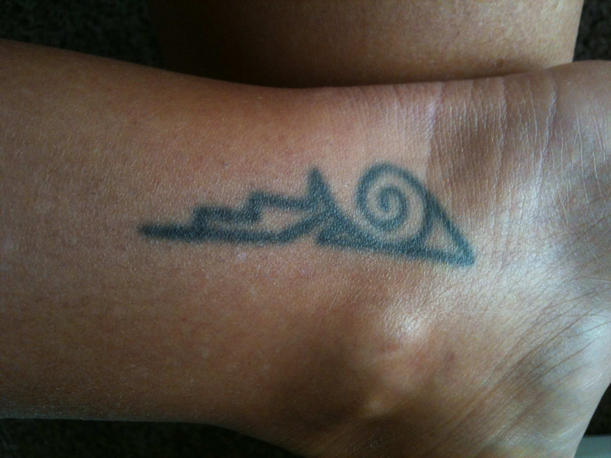 The swirl represents water or waves, the right side is a pueblo/earth ...